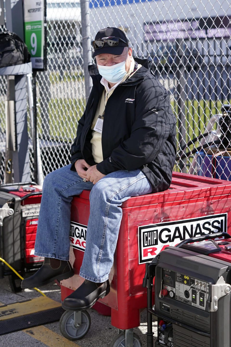Chip Ganassi, owner of Chip Ganassi Racing, takes a break outside his pit stall during a practice session for the Rolex 24 hour race at Daytona International Speedway, Friday, Jan. 29, 2021, in Daytona Beach, Fla. (AP Photo/John Raoux)