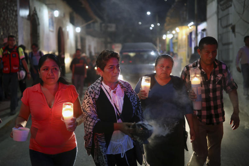 Mourners carry candles as they walk with the hearse bringing the body of Maricela Vallejo, the slain 27-year-old mayor of Mixtla de Altamirano, to her aunt's house for a wake in Zongolica, Veracruz state, Mexico, Thursday, April 25, 2019. Vallejo, her husband, and a driver were assassinated Thursday by multiple gunmen as they drove along a highway. (AP Photo/Felix Marquez)