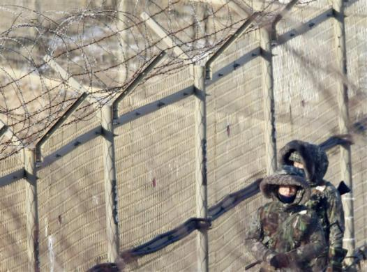 Soldiers walk along a barbed wire fence near the demilitarized zone (DMZ) which separates the two Koreas in Paju, about 50 km (31 miles) north of Seoul, December 27, 2011.