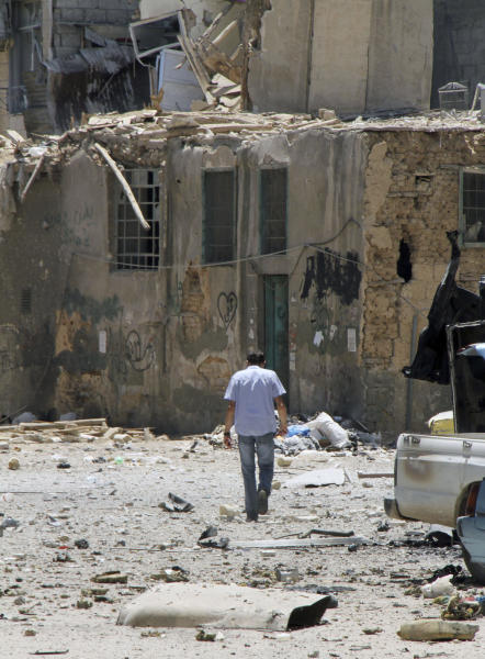 In this photo taken during a government-organized tour, a Syrian man walks on a damaged street after the Syrian troops regained control of the district of Midan, in the southern part of Damascus, Syria, Friday, July 20, 2012. Syrian troops and tanks on Friday drove rebels from a Damascus neighborhood where some of the heaviest of this week's fighting in the capital left cars gutted and fighters' bodies in the streets. Hundreds of people were killed in a single day, activists said, as the military struggles to regain momentum after a stunning bombing against the regime's leadership. (AP Photo/Bassem Tellawi)
