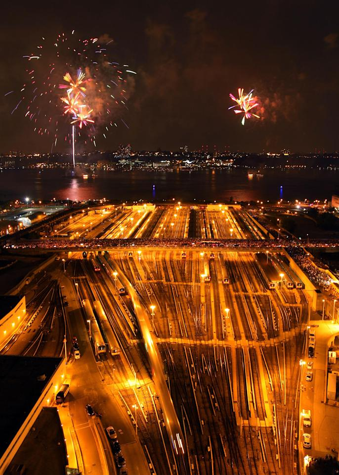 Trains run through Hudson Yard in New York as fireworks light up the sky over the Hudson River during the Macy's Fourth of July fireworks show Wednesday, July 4, 2012. (AP Photo/CX Matiash)