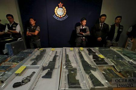 Police officers stand in front of air rifles seized along with explosives, during a news conference in Hong Kong, China June 15, 2015. REUTERS/Bobby Yip
