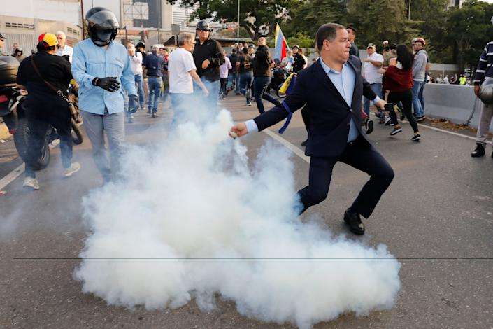 An opponent to Venezuela's President Nicolas Maduro returns a tear gas canister to soldiers who launched it at a small group of civilians and rebel troops gathered outside La Carlota air base in Caracas, Venezuela, Tuesday, April 30, 2019. Venezuelan opposition leader Juan Guaidó took to the streets with activist Leopoldo Lopez and a small contingent of heavily armed troops early Tuesday in a bold and risky call for the military to rise up and oust socialist leader Nicolas Maduro. (Photo: Ariana Cubillos/AP)