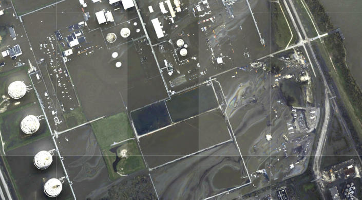 """This image provided by NOAA taken Tuesday, Aug. 31, 2021 and reviewed by The Associated Press shows oil slicks at the flooded Phillips 66 Alliance Refinery in Belle Chasse, La. State and federal regulators responded to the spill site after AP provided the photos of the spill Wednesday and the company acknowledged a """"sheen of unknown origin"""" at its flooded refinery. (NOAA via AP)"""