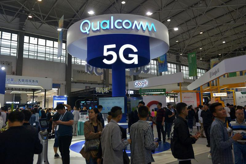 FILE PHOTO: Visitors are seen by a booth of Qualcomm Inc at the China International Big Data Industry Expo in Guiyang