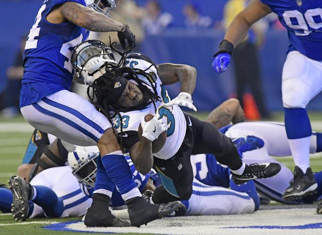 <p>Jacksonville Jaguars running back Chris Ivory (33) has his helmet ripped off by Indianapolis Colts linebacker Antonio Morrison (44) at Lucas Oil Stadium. Mandatory Credit: Thomas J. Russo-USA TODAY Sports </p>