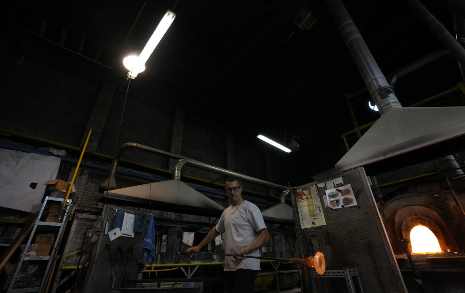 A glass-worker heats glass in a methane powered ovens in a factory in Murano island, Venice, Italy, Thursday, Oct. 7, 2021. The glassblowers of Murano have survived plagues and pandemics and have transitioned to highly prized artistic creations to outrun competition from Asia, but surging energy prices may be their doom. (AP Photo/Antonio Calanni)