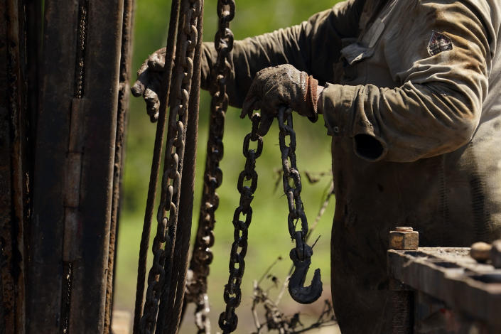 A well worker moves equipment at a site on the Rooke family ranch where an orphaned oil well was plugged, Tuesday, May 18, 2021, near Refugio, Texas. Oil and gas drilling began on the ranch in the 1920s and there were dozens of orphaned wells that needed to be plugged for safety and environmental protection. (AP Photo/Eric Gay)