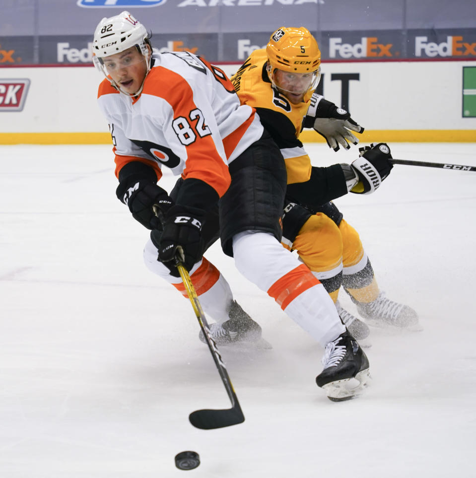 Philadelphia Flyers' Connor Bunnaman (82) controls the puck in front of Pittsburgh Penguins' Mike Matheson (5) during the second period of an NHL hockey game Thursday, March 4, 2021, in Pittsburgh. (AP Photo/Keith Srakocic)