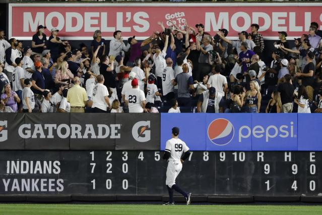 New York Yankees right fielder Aaron Judge watches as fans attempt to catch a ball hit by Cleveland Indians' Carlos Santana for a two-run home run during the fourth inning of a baseball game Thursday, Aug. 15, 2019, in New York. (AP Photo/Frank Franklin II)
