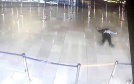 A picture taken of a television screen shows a man lying on the ground of a terminal building at Paris' Orly airport after he was shot by French security forces for taking a weapon from a soldier - Credit: AFP/Getty Images