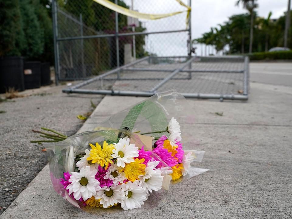 Flowers lie at the scene where a driver slammed into spectators at the start of a Pride parade Saturday evening, killing one man and seriously injuring another, Sunday 20 June 2021 (AP)