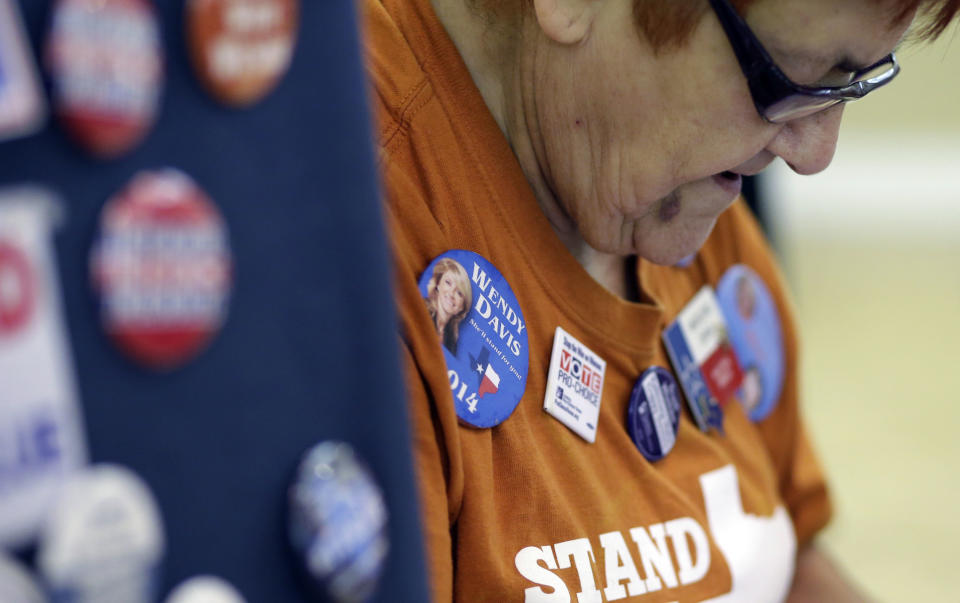 Madeleine Dewar sells political buttons to supporters gathered for an announcement watch party for State Sen. Wendy Davis, Thursday, Oct. 3, 2013, in San Antonio. Davis formally announced her campaign for governor, becoming the first Democrat to make an official bid for a statewide office. (AP Photo/Eric Gay)