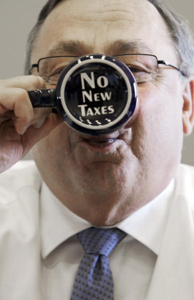 """In this Friday, April 27, 2012 photo, Gov. Paul LePage takes a sip out of a coffee mug displaying a """"no new taxes"""" message on the bottom during an interview with the Associated Press at his office at the State House in Augusta, Maine. Critics are putting pressure on LePage to apologize for referring to the Internal Revenue Service as """"the new Gestapo"""" during his radio address Saturday, July 7, 2012. (AP Photo/Pat Wellenbach)"""