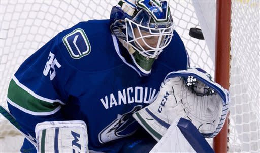 A shot by Dallas Stars right wing Reilly Smith goes past Vancouver Canucks goalie Cory Schneider (35) for a goal during the first period of an NHL hockey game in Vancouver, British Columbia, Friday, Feb. 15, 2013. (AP Photo/The Canadian Press, Jonathan Hayward)