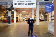 FILE - In this Nov. 16, 2020, file photo, a sign points to a mask mandate at the Grand Central Market in Los Angeles. Gov. Gavin Newsom announced Monday, Nov. 16, 2020, that due to the rise of COVID-19 cases, some counties have been moved to the state's most restrictive set of rules, which prohibit indoor dining. The new rules begin Tuesday, Nov. 17. (AP Photo/Marcio Jose Sanchez, File)
