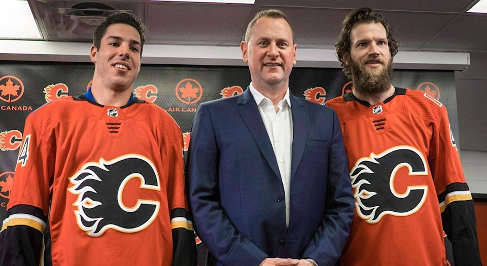 Travis Hamonic (left) and Mike Smith (right) are introduced by Flames GM Brad Treliving (center). (Jeff McIntosh/CP)