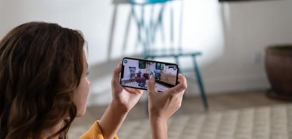 A woman taking a picture with an iPhone XS Max.