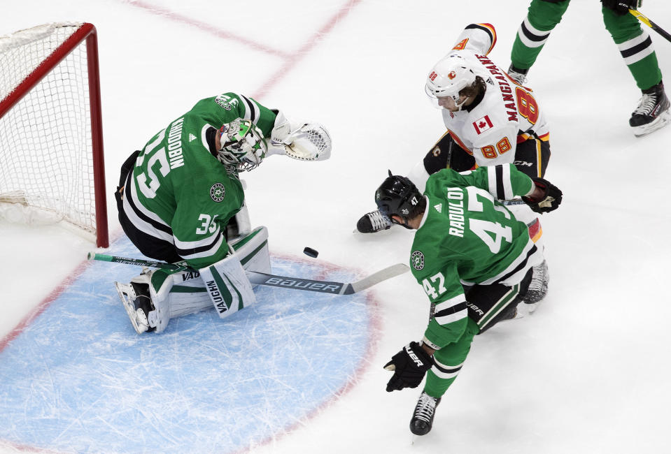 Calgary Flames' Andrew Mangiapane (88) is stopped by Dallas Stars goalie Anton Khudobin (35) as Alexander Radulov (47) defends during the first period in Game 1 of an NHL hockey Stanley Cup first-round playoff series, Tuesday, Aug. 11, 2020, in Edmonton, Alberta. (Jason Franson/The Canadian Press via AP)