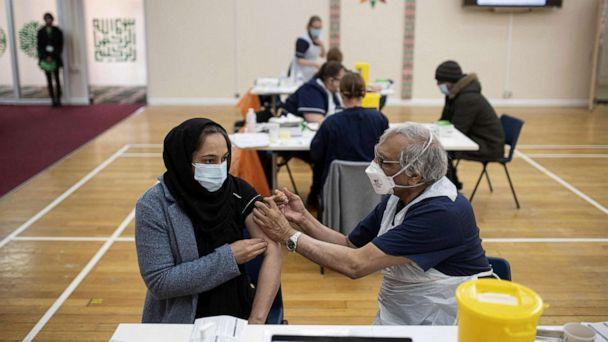 PHOTO: A health worker administers a dose of the AstraZeneca/Oxford Covid-19 vaccine to a patient at a vaccination centre set up at the Karimia Institute Islamic centre and Mosque in Nottingham, England, April 6, 2021. (Oli Scarff/AFP via Getty Images)