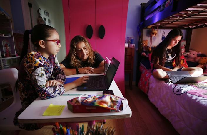 """Sofia Quezada assists her daughters Priscilla, left, and Paulette Guerrero with virtual class from their Boyle Heights home. Tech issues on the first day of class drove 9-year-old Priscilla to tears. <span class=""""copyright"""">(Al Seib / Los Angeles Times)</span>"""