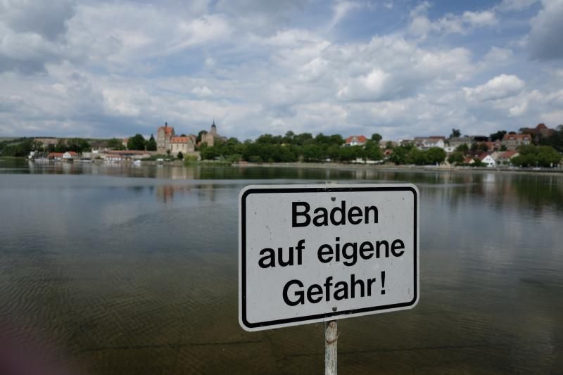 """08 June 2020, Saxony-Anhalt, Seeburg: A sign with the inscription """"Bathing at your own risk"""" stands on the shore of the sweet lake at the lake terraces Seeburg. This bathing area was criticised in the annual bathing water report. If you are looking for cooling off at German lakes, rivers and coasts this summer, you can look forward to predominantly excellent water quality. Only eight of the 2291 German bathing sites investigated failed this time in the annual evaluation because too many questionable bacteria were discovered in the water. Photo: Sebastian Willnow/dpa-Zentralbild/dpa (Photo by Sebastian Willnow/picture alliance via Getty Images)"""