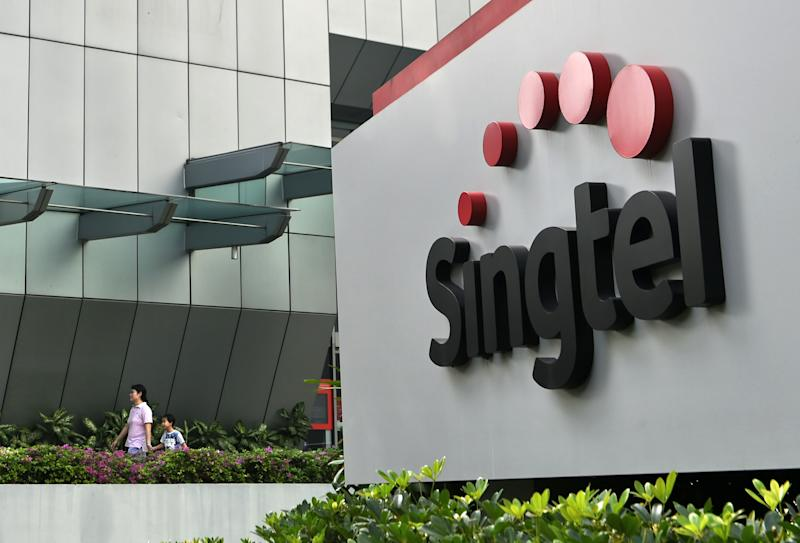 A woman and a child walk out of the Singapore Telecommunications (Singtel) building in Singapore on February 12, 2016. Singtel reported a 1.7 per cent fall in third-quarter net profit of 683 million US dollar for the three months ended December, compared with 694 million US dollar a year ago, as adverse currency movements and investments offset growing mobile data usage by its customers. AFP PHOTO / ROSLAN RAHMAN (Photo by Roslan RAHMAN / AFP) (Photo by ROSLAN RAHMAN/AFP via Getty Images)
