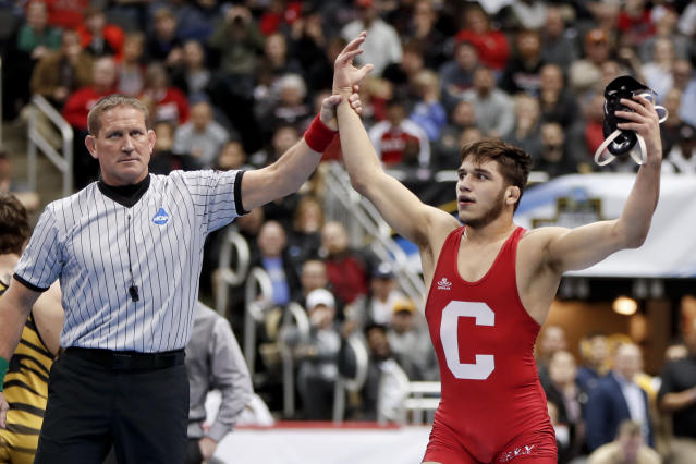 Cornell's Yianni Diakomihalis, right, has his arm raised after defeating Misouri's Jaydin Eirman in their 141-pound match in the semifinals of the NCAA wrestling championships, Friday, March 22, 2019, in Pittsburgh. Diakomihalis won and will face Ohio State's Joey McKenna in the finals Saturday. (AP Photo/Keith Srakocic)