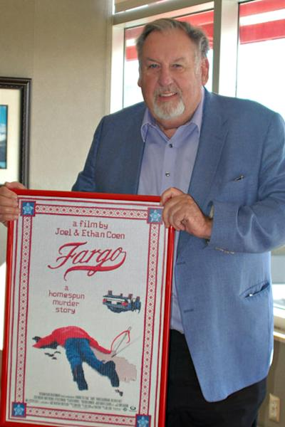 """In this photo taken Oct. 10, 2012, Fargo Mayor Dennis Walaker poses with a poster of the Coen Bros. film that catapulted the North Dakotan town to worldwide fame. Though many residents initially weren't keen on the """"you betchas"""" and """"ya sures"""" of the film's characters, the city eventually embraced the movie and officials say they're excited about a recently announced Coen-created TV series of the same name. (AP Photo/Dave Kolpack)"""