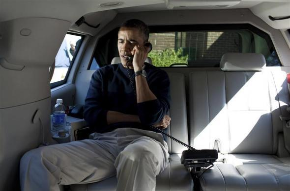 President Barack Obama talks on a phone with Afghanistan's President Hamid Karzai from his vehicle outside the Jane E. Lawton Community Center in Chevy Chase, Maryland, in this handout photograph taken and released on March 11, 2012.