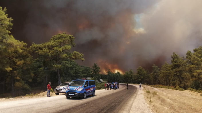 Paramilitary police officers and people watch as a wildfire fanned by strong winds rage near the Mediterranean coastal town of Manavgat, Antalya, Turkey, Wednesday, July 28, 2021. Authorities evacuated homes in Manavgat as a wildfire raged Wednesday through a forest. Gendarmerie forces helped move residents out of four neighborhoods in the town out of the fire's path as firefighters worked to control the blaze, the Manavgat district governor Mustafa Yigit told the state-run Anadolu Agency. (Arif Kaplan/IHA via AP)