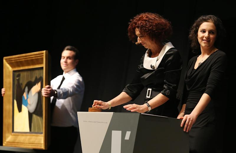 """Judit Virag (C) knocks down the auction hammer at the Judit Virag Gallery in Budapest on December 13, 2014, next to the painting """"Sleeping woman with black vase"""" by Hungarian artist Robert Bereny (AFP Photo/Ferenc Isza)"""