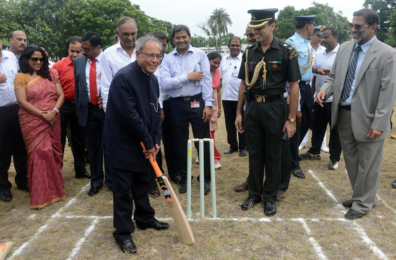 Indian President Pranab Mukherjee poses with a bat during the inauguration of the new cricket grounds at the Presidential Estate to mark his one year in office, in New Delhi on July 25, 2013. Mukherjee, 77, an active politician for over four decades, has completed his first year in office as President. AFP PHOTO/RAVEENDRAN        (Photo credit should read RAVEENDRAN/AFP/Getty Images)