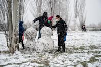 Varias personas hacen un muñeco de nieve en un parque de Madrid. (Photo by Marcos del Mazo/LightRocket via Getty Images)