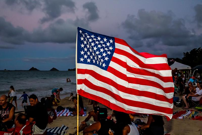 An American Flag waves in the sand as crowds and families gather to watch the spectacular Fourth of July fireworks show at the world famous travel destination of Kailua Beach with Lanikai Beach in the distance. Sunset in Hawaii on the Island of Oahu.