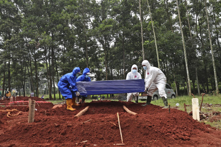 Workers in protective suits prepare to lower a coffin containing the body of a COVID-19 victim into a grave at Cipenjo cemetery in Bogor, West Java, Indonesia, Wednesday, July 14, 2021. The world's fourth most populous country has been hit hard by an explosion of COVID-19 cases that have strained hospitals on the main island of Java.(AP Photo/Achmad Ibrahim)
