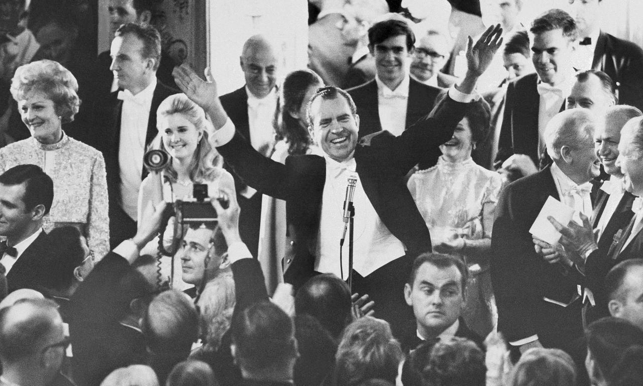 Pres. Richard Nixon, center, greets the crowd at the Mayflower Hotel Inaugural Ball, Jan. 21, 1969, Washington, D.C. From left are Pat Nixon, daughter Tricia Nixon, Julie (hidden) and David Eisenhower. The rest of the group is unidentified. (AP Photo/Gary Settle)