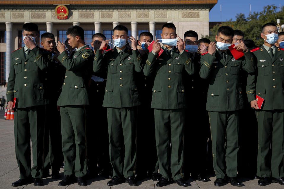 Chinese paramilitary policemen put on their face masks to help curb the spread of the coronavirus arrive to the Great Hall of the People to attend the commemorating conference on the 70th anniversary of China's entry into the 1950-53 Korean War, in Beijing Friday, Oct. 23, 2020. (AP Photo/Andy Wong)