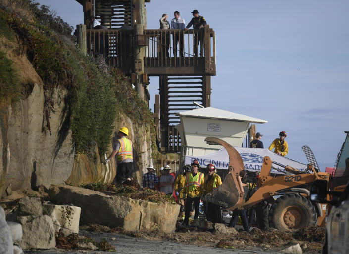 Search and rescue personnel work at the site of a cliff collapse at a popular beach Friday, Aug. 2, 2019, in Encinitas, Calif. At least one person was reportedly killed, and multiple people were injured, when an oceanfront bluff collapsed Friday at Grandview Beach in the Leucadia area of Encinitas, authorities said. (AP Photo/Denis Poroy)