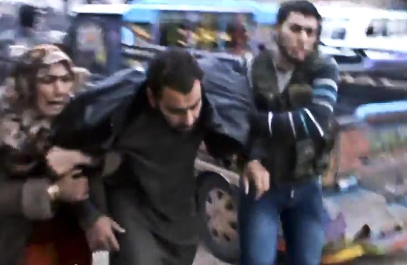 This Sunday, Dec. 23, 2012 image taken from video obtained from the Shaam News Network, which has been authenticated based on its contents and other AP reporting, shows Syrians helping a wounded man after a government airstrike hit the Hama Suburb of Halfaya, Syria. A government airstrike Sunday on a bakery in a rebel-held town in central Syria killed tens of people, which left scattered bodies and debris up and down a street, and more than a dozen wounded were trapped in tangled heap of dirt and rubble, activists said. (AP Photo/Shaam News Network via AP video)