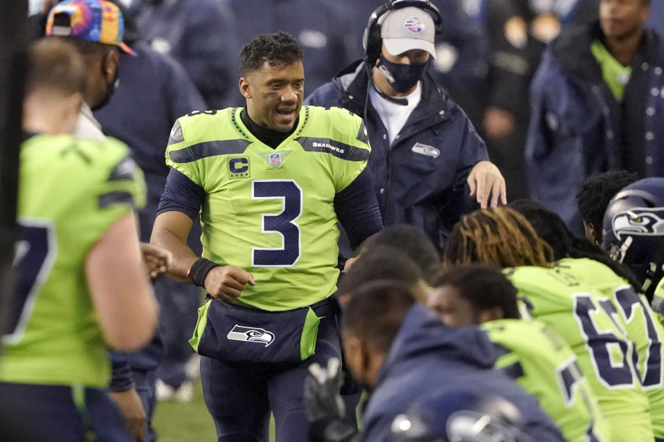 Seattle Seahawks quarterback Russell Wilson (3) talks with teammates on the bench during the first half of an NFL football game, Sunday, Oct. 11, 2020, in Seattle. (AP Photo/Ted S. Warren)
