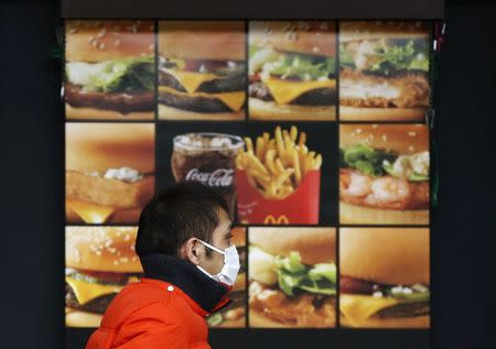 A man walks past an advertisement showing McDonald's burgers, fries and a drink, outside a McDonald's store in Tokyo December 16, 2014.  REUTERS/Issei Kato