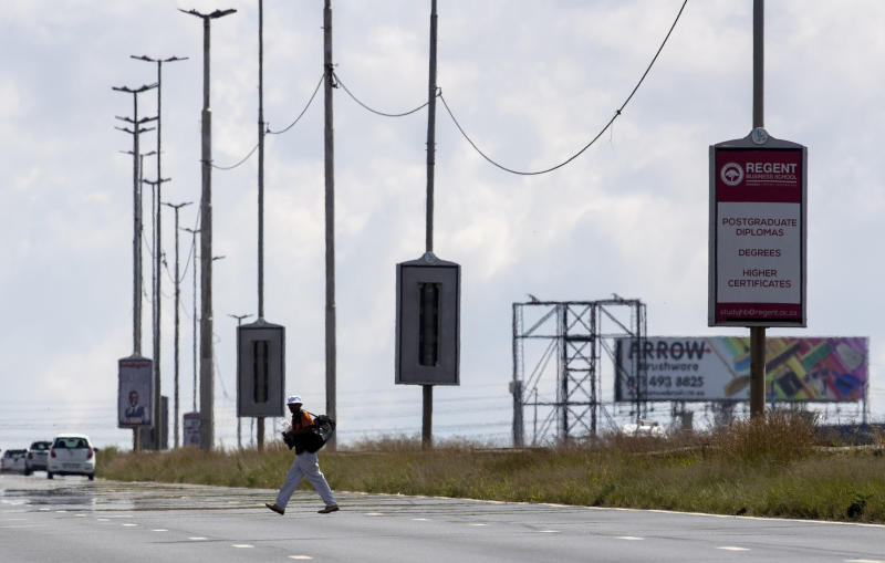 A man crosses on M2, a major highway on foot, in Johannesburg, South Africa, Friday, March 27, 2020. South Africa went into a nationwide lockdown for 21 days in an effort to mitigate the spread to the coronavirus. The new coronavirus causes mild or moderate symptoms for most people, but for some, especially older adults and people with existing health problems, it can cause more severe illness or death. (AP Photo/Themba Hadebe)