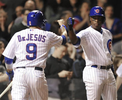 Chicago Cubs' Alfonso Soriano right, celebrates with teammate David DeJesus (9) after DeJesus scored on an Anthony Rizzo single during the seventh inning of a baseball game against the Colorado Rockies in Chicago, Wednesday, May 15, 2013. (AP Photo/Paul Beaty)