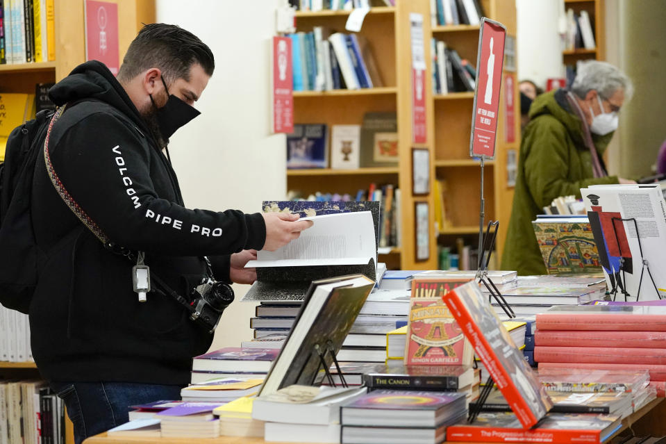 FILE- In this Saturday, Nov. 28, 2020, file photo, customers browse while shopping for books at the Strand Bookstore, an independent family owned bookstore founded in 1927 in New York. On Thursday, the American Booksellers Association said that membership increased from 1,635 to 1,701 since May 2020, the additions a combination of brand new stores and existing stores that had not previously been part of the independents' trade group. While association CEO Allison Hill and others had feared that hundreds of stores could go out of business during the 2020-21 holiday season, the ABA so far has only tallied 14 closings in 2021, along with more than 70 last year. (AP Photo/Mary Altaffer, File)