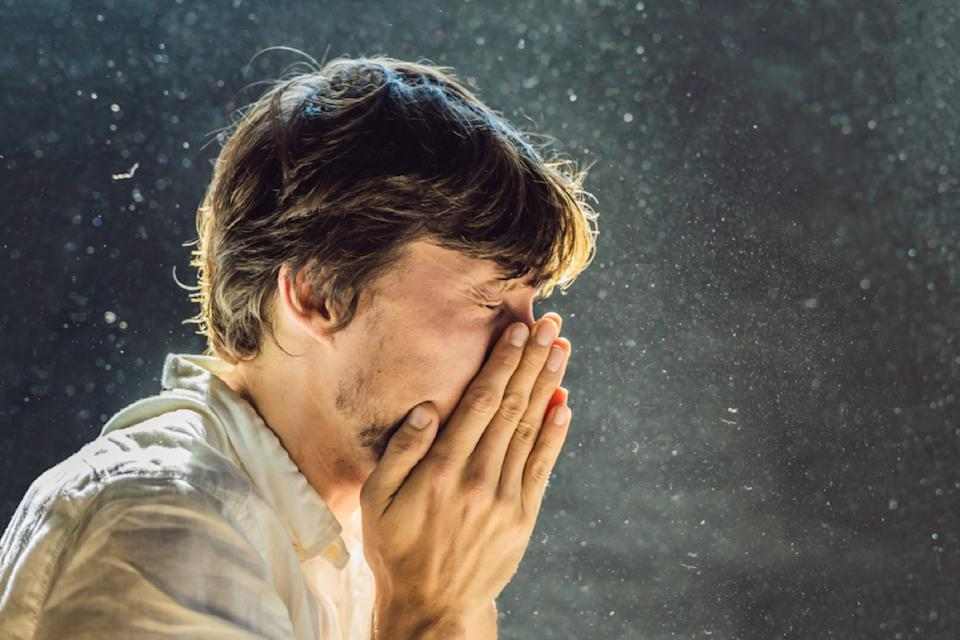white man sneezing with droplets in the air