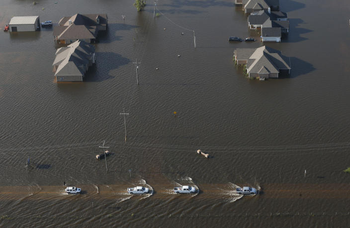 <p>Trucks drive on a flooded rowdy past flooded houses in the aftermath of Tropical Storm Harvey in Orange, Texas, Thursday, Aug. 31, 2017. (Photo: Gerald Herbert/AP) </p>