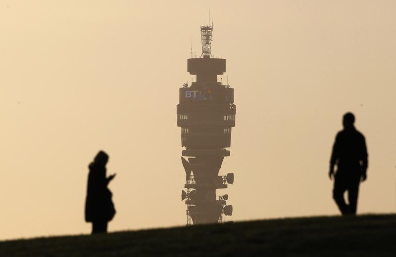 The BT communication tower is seen in the background as people walk on Primrose Hill in London
