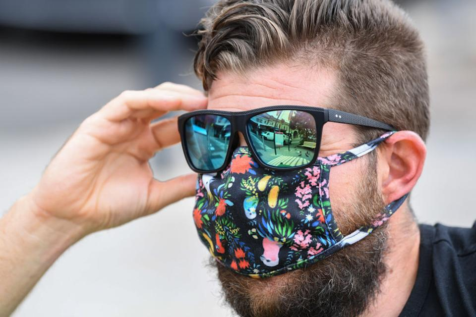 A man wears sunglasses and a face mask in the suburb of Milson's Point in Sydney, Australia.