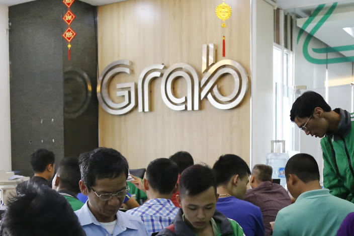 FILE - In this May 24, 2017, file photo, applicants fill in forms to join Grab Vietnam at the company's office in Hanoi, Vietnam. Southeast Asia's largest ride-hailing company, Grab Holdings, said Tuesday, April 13, 2021 that it plans to merge with U.S.-based Altimeter Growth Capital in a deal that would value it at nearly $40 billion in preparation for an initial public offering in the U.S. (AP Photo/Tran Van Minh, File)